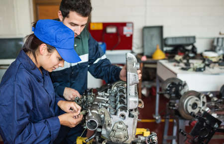trainee: Focused trainee and instructor checking engine in workshop LANG_EVOIMAGES