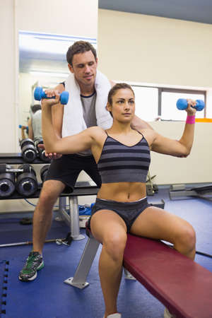 correcting: Trainer correcting toned brunette lifting dumbbells in weights room of gym LANG_EVOIMAGES