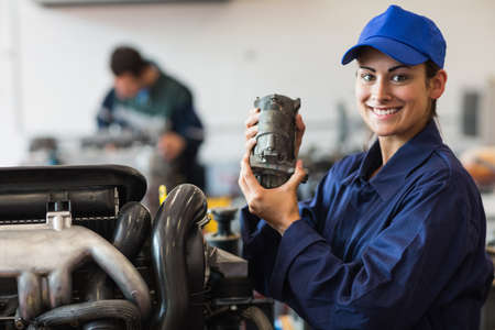 trainee: Happy trainee showing part of a machine in workshop LANG_EVOIMAGES