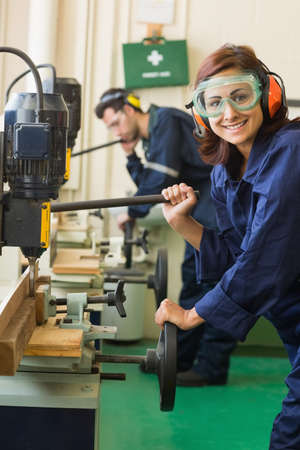 trainee: Cheerful trainee with safety glasses drilling wood in workshop