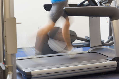 low section view: Low section side view of a healthy man running on treadmill at fitness studio