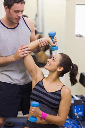 correcting: Instructor correcting woman lifting dumbbells in weights room of gym LANG_EVOIMAGES