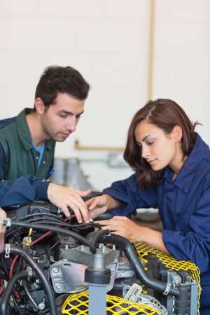 trainee: Serious instructor and trainee checking a machine in workshop