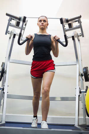 tied hair: Determined woman training her arms in weights room of gym