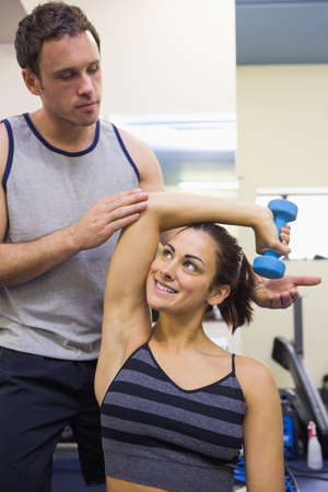 correcting: Trainer correcting smiling woman lifting dumbbells in weights room of gym