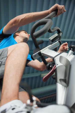 man working out: Low angle view of a determined young man working out at spinning class in gym LANG_EVOIMAGES