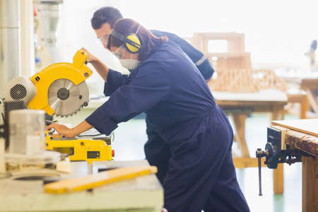 trainee: Concentrating trainee sawing piece of wood in workshop