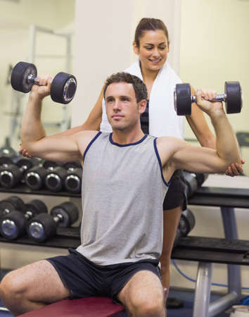 correcting: Trainer correcting attractive man lifting dumbbells in weights room of gym