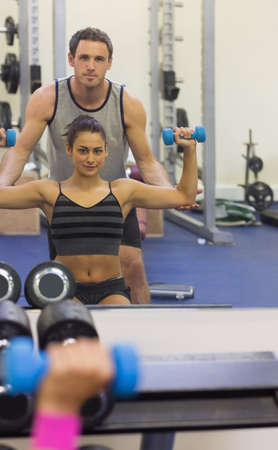 aligning: Reflection of instructor correcting woman lifting dumbbells in weights room of gym