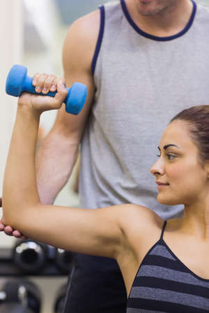 correcting: Trainer correcting calm woman lifting dumbbells in weights room of gym LANG_EVOIMAGES