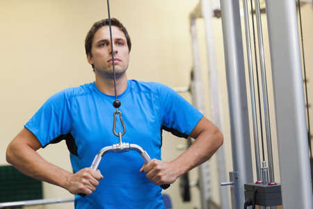 lat: Determined sporty young man doing exercises in the gym on lat machine