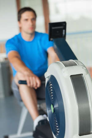 man working out: Determined young man working out on row machine in fitness studio LANG_EVOIMAGES
