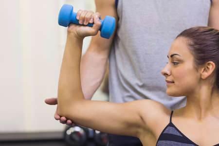 correcting: Trainer correcting woman lifting dumbbells in weights room of gym