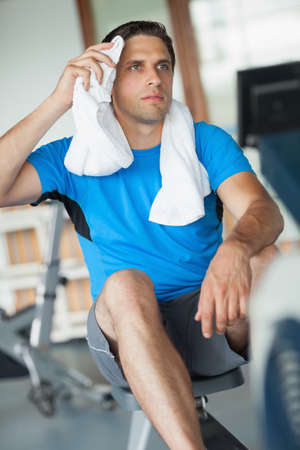 man working out: Tired young man working out on row machine in fitness studio