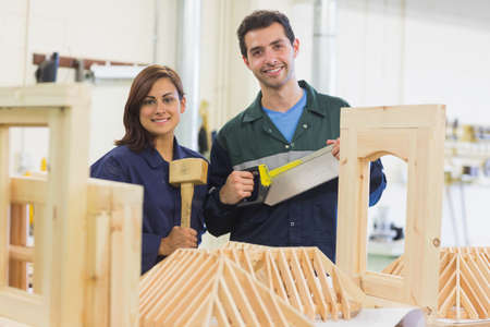 trainee: Cheerful trainee and instructor standing behind construction in workshop
