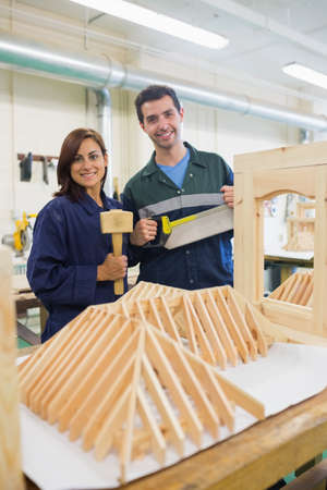 trainee: Smiling trainee and instructor standing behind construction in workshop LANG_EVOIMAGES