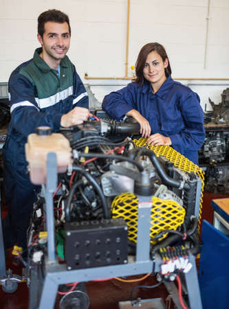 trainee: Smiling instructor and trainee standing behind machine in workshop