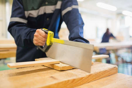sawing: Carpenter sawing wood in workshop