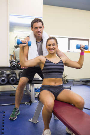 correcting: Trainer correcting smiling brunette lifting dumbbells in weights room of gym LANG_EVOIMAGES