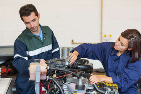 trainee: Focused instructor and trainee checking a machine in workshop