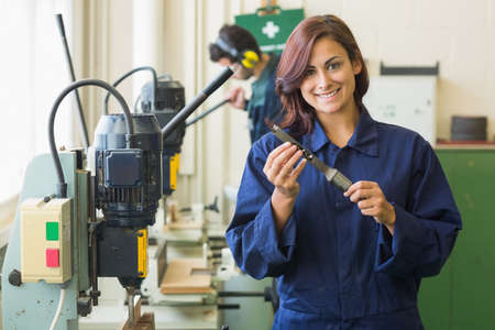 trainee: Smiling trainee holding tool in workshop