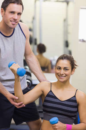 correcting: Instructor correcting happy woman lifting dumbbells in weights room of gym
