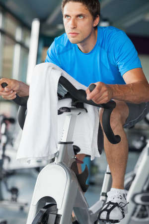 man working out: Determined young man working out at spinning class in gym