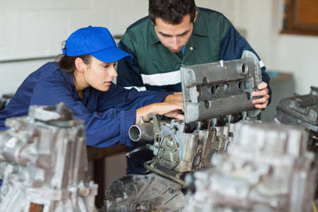 trainee: Focused trainee repairing engine with instructor in workshop LANG_EVOIMAGES