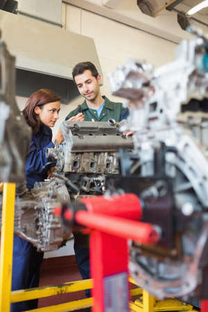 trainee: Concentrating trainee and instructor repairing an engine in workshop LANG_EVOIMAGES