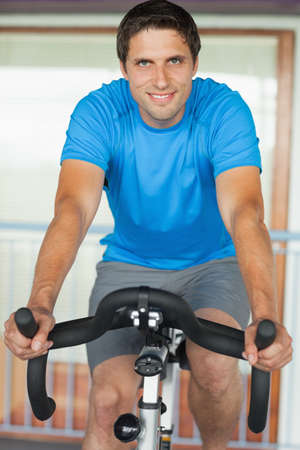 man working out: Retrato de un hombre joven y sonriente que se resuelve en clase de spinning en el gimnasio