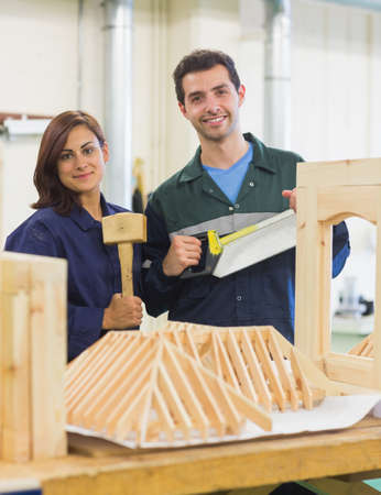 gleeful: Gleeful trainee and instructor standing behind construction in workshop