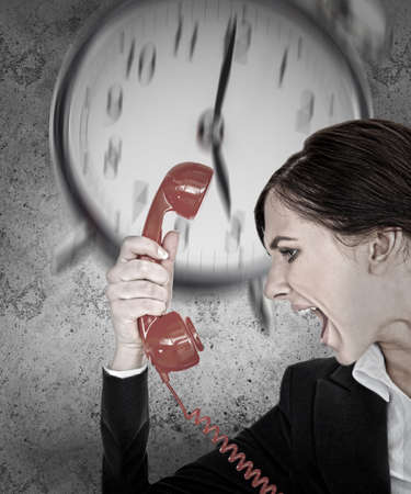 under pressure: Businesswoman under pressure with deadline shouting down the phone