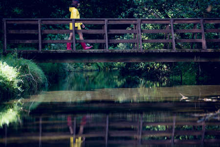 пышной листвой: Side view of a woman walking on footbridge over forest waterfall amid lush foliage LANG_EVOIMAGES