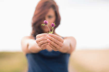 ���clear sky���: Blurred young woman holding out wild flowers in field against clear sky