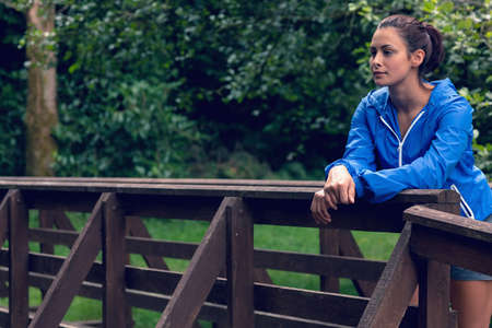 body concern: Thoughtful healthy woman standing on footbridge during exercise