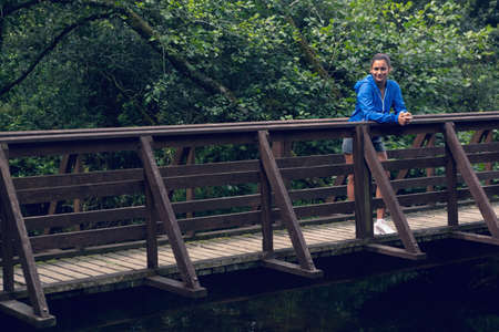 body concern: Portrait of a smiling healthy young woman standing on footbridge during exercise