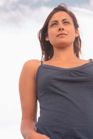tank top: Low angle view of a young woman in tank top against the sky
