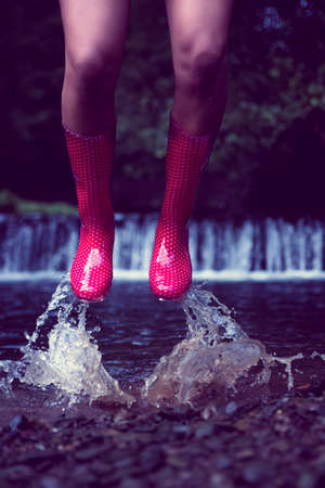 gumboots: Close up low section of a woman in red gumboots jumping in water