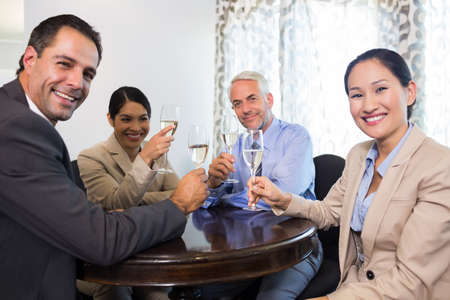 toasting wine: Portrait of business colleagues toasting wine glasses at the office