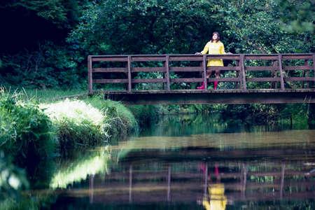 пышной листвой: Woman standing on footbridge over lake and amid lush foliage