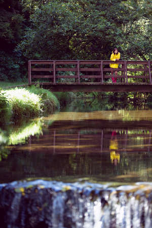 lush foliage: Woman standing on footbridge over lake and amid lush foliage