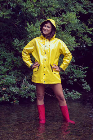 Portrait of a smiling young woman in yellow raincoat and red gumboots standing against trees