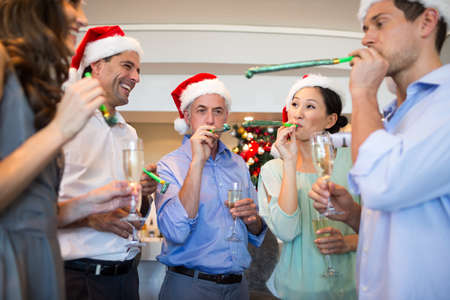 champagne flutes: Happy people in Santas hats with champagne flutes and noise makers at the bar
