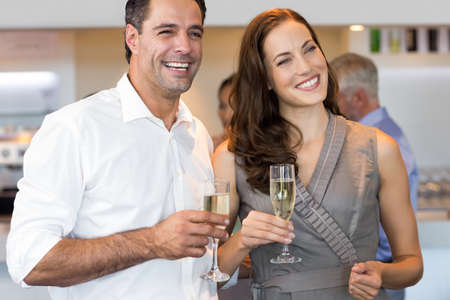 champagne flutes: Portrait of cheerful couple with champagne flutes at the bar