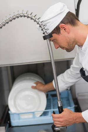 commercial kitchen: Kitchen porter cleaning plates in sink in a commercial kitchen LANG_EVOIMAGES