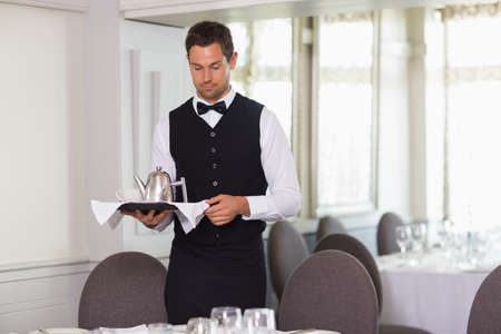 stand teapot: Handsome waiter holding tray and setting table in a fancy restaurant