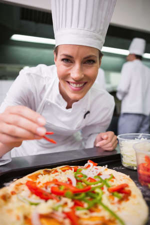 sprinkling: Happy chef sprinkling pepper on a pizza in a commercial kitchen