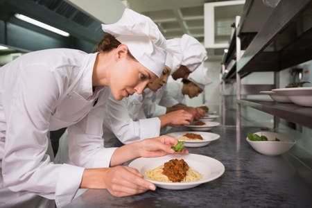 basil  leaf: Row of chefs garnishing spaghetti dishes with basil leaf in a commercial kitchen LANG_EVOIMAGES