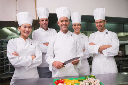 trainees: Head chef standing with happy trainees in a commercial kitchen