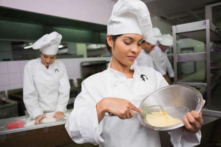 whisking: Happy chef whisking bowl of eggs in a commercial kitchen